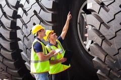 Arbetare som kontrollerar gummihjul
