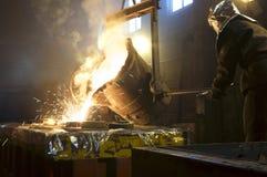 Arbetare som kontrollerar metall som smälter i pannor Arbetaren fungerar på den metallurgical växten Vätskemetallen hälls royaltyfri bild