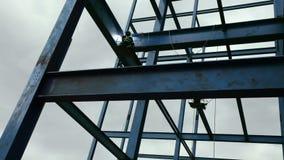 Arbetare som löder strukturen för stålstråle på nybygge lager videofilmer