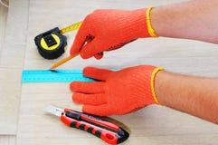 Arbetare som mätas och markeras på linoleet Bitande linoleum för arbetare Måttband Royaltyfri Fotografi