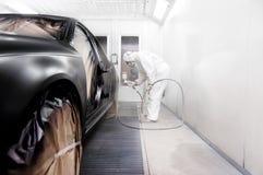 Arbetare som målar en svart bil i ett specialt garage Fotografering för Bildbyråer