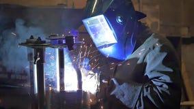 Arbetare som maler och svetsar i en fabrik Svetsning på en industrianläggning långsam rörelse lager videofilmer