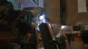 Arbetare som maler och svetsar i en fabrik Svetsning på en industrianläggning långsam rörelse arkivfilmer