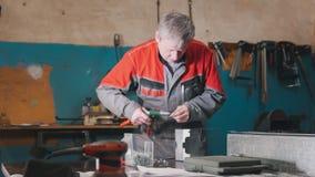 Arbetare som monterar metalldelen vid handen med plattång, hjälpmedel för malande metall och metalldetaljer i förgrunden Royaltyfri Fotografi