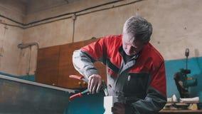 Arbetare som monterar metalldelen vid handen med plattång, hjälpmedel för malande metall och metalldetaljer i förgrunden Royaltyfri Foto