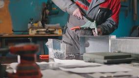 Arbetare som monterar metalldelen vid handen med plattång, hjälpmedel för malande metall och metalldetaljer i förgrunden Royaltyfri Bild