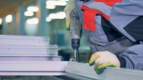 Arbetare som monterar PVC-dörrar och fönster genom att använda den industriella skruvmejseln stock video