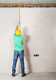 Arbetare som mäter murbrukväggen Arkivfoton
