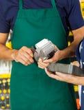Arbetare som nallar kreditkorten med det hållande hjälpmedlet för kvinna Royaltyfri Foto