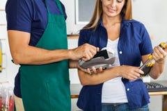 Arbetare som nallar kreditkorten med kvinnainnehavet Royaltyfri Fotografi