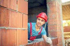 Arbetare som ok visar handtecknet på konstruktionsplats Byggnadstekniker med godkännande konstruktion för kvalitets- kontroll Royaltyfria Bilder