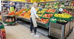 Arbetare som ordnar frukter i supermarket Arkivbild