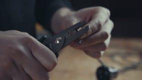 Arbetare som reparerar en elektrisk kabel eller binder genom att använda plattång fotografering för bildbyråer