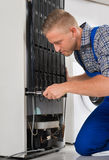Arbetare som reparerar kylskåpet i hus royaltyfria foton