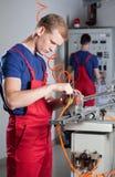 Arbetare som reparerar maskinen Arkivbild