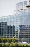 Arbetare som reparerar tvagningfönstret av parlamentbyggnad Arkivfoto