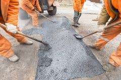 Arbetare som reparerar vägen med skyfflar, fyller asfaltkörbanareparation Arkivfoton
