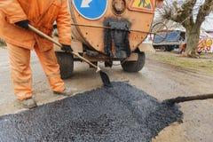 Arbetare som reparerar vägen med skyfflar, fyller asfaltkörbanareparation Arkivbild
