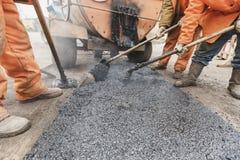 Arbetare som reparerar vägen med skyfflar, fyller asfaltkörbanareparation Arkivbilder