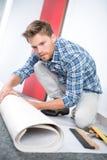 Arbetare som rullar ut material för golv Fotografering för Bildbyråer
