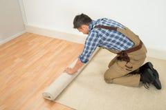 Arbetare som rullar ut matta på golv Arkivbilder