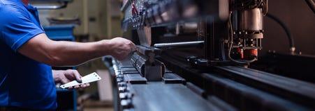 Arbetare som rymmer en metallplatta arkivfoto