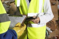 Arbetare som rymmer skrivplattor i bransch Arkivfoto