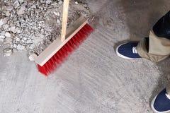 Arbetare som sopar spillror på golvet med en kvast Royaltyfri Fotografi