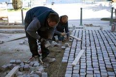 Arbetare som ställer in - upp trottoarer arkivbild