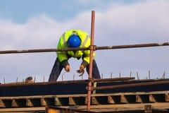 Arbetare som sticker stänger för metallstänger in i ramförstärkningen arkivfoton