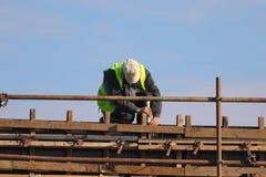 Arbetare som sticker stänger för metallstänger in i ramförstärkningen arkivbilder