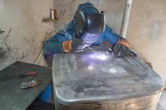 Arbetare som svetsar den aluminum behållaren Arkivbild