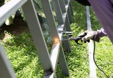 Arbetare som svetsar en ståljärnstång för ett nytt staket Frame royaltyfri foto