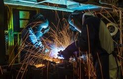 Arbetare som svetsar i en bilfabrik Arkivfoto