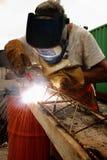 Arbetare som svetsar stål med den elektriska svetsningmaskinen Arkivbilder