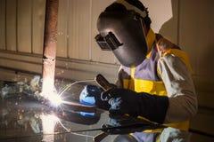 Arbetare som svetsar ståldelen Arkivfoto