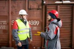 Arbetare som talar till arbetsledaren i skeppsdockor arkivfoton