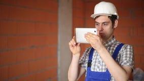 Arbetare som tar bilder och gör beräkningar med din minnestavla arkivfilmer