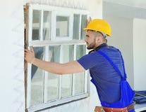 Arbetare som tar bort det gamla fönstret arkivfoto