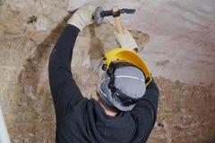 Arbetare som tar bort murbruk från väggen med hjälpmedel Royaltyfria Foton