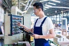 Arbetare som trycker på knappar på CNC-maskinen i fabrik Royaltyfria Foton