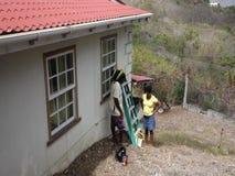 Arbetare som utför underhåll på ett hus i vändkretsarna arkivfilmer