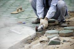 Arbetare stenlägger cementkvarteret royaltyfri bild