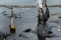 Arbetare tar bort och gör ren upp spilld råolja med absorberande välling Arkivfoton