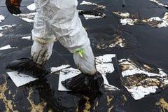 Arbetare tar bort och gör ren upp spilld råolja med absorberande välling Royaltyfri Bild