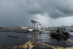 Arbetare tar bort och gör ren upp spilld råolja med absorberande välling Fotografering för Bildbyråer