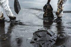 Arbetare tar bort och gör ren upp spilld råolja med absorberande välling Royaltyfria Foton