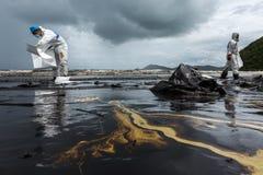 Arbetare tar bort och gör ren upp spilld råolja med absorberande välling Royaltyfria Bilder