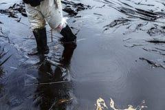 Arbetare tar bort och gör ren upp spilld råolja med absorberande välling Royaltyfri Fotografi
