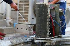 Arbetare till rengörande spolekylare av luftkonditioneringsapparaten vid vatten för rengöring ett damm på väggen i kundhem när un fotografering för bildbyråer